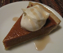 Pumpkin pie with whipped cream and maple syrup